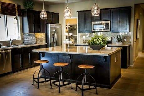 A Remarkable Kitchen Design With Cabinets, Refrigerator And Center Table  With Three Chairs Arranged To