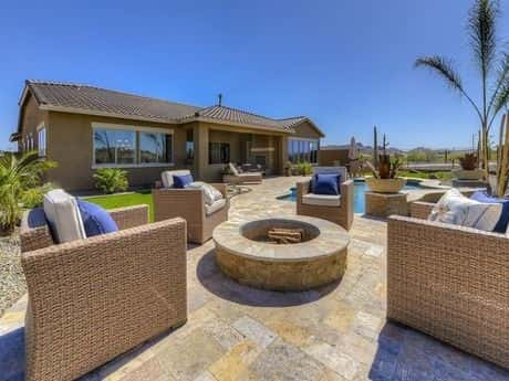 Woven rectangular chairs with pads and pillows are surrounding a firepit in a brilliant outdoor decoration.