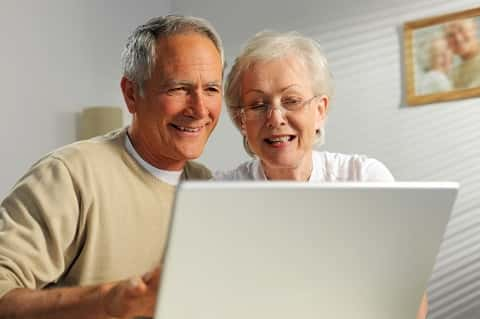 Elderly couple smiling happily at a laptop computer. Hanging on the wall in the background is a picture of the couple.