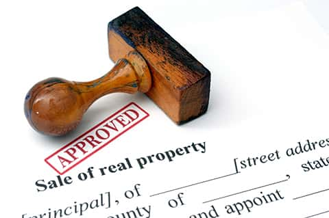 A document for the sale of real property already stamped approved, with the stamp on the document.