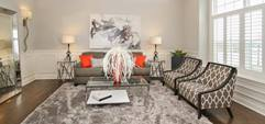 A beautiful and simply decorated room with grey and white themes with a touch of orange as well.