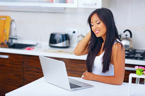 A woman with her one hand on her head as she examines information on her laptop in her kitchen.