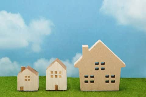 Simple representation of three houses on a lawn. The houses increase in size from left to right.
