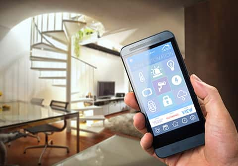 A hand holding a smartphone displaying the home automation app. The app has different options and the video camera has been selected.