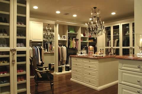 Closet filled with varieties of shoes and clothes with a chandelier hanging from the ceiling.