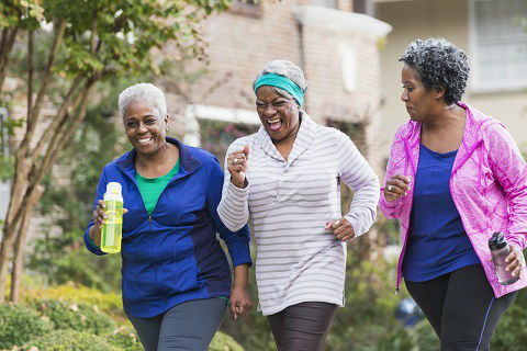 Three senior ladies running and laughing. All these three ladies are equipped in sport clothes and two of them have water bottles in their hands.