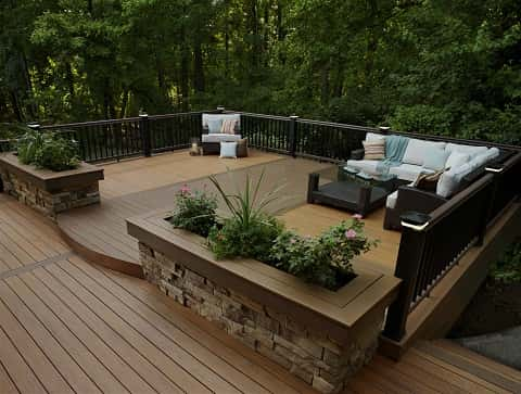 Wooden balcony with seats and table creating a perfect view into a forest of trees.
