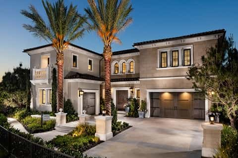 A giant luxury house is lighted during the evening. In front of the house are two palm trees and a small fence.