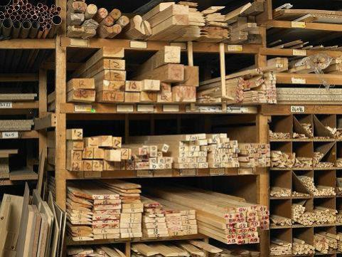 Wooden shelve demarcated into different sections with different labeled sizes of planks arranged in different sections.