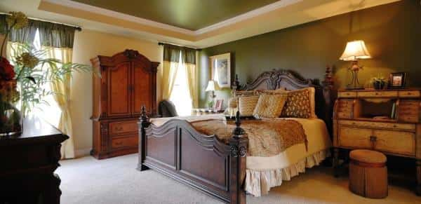 An example of a bedroom decorated with classy furniture pieces all arranged neatly and all with diferent rich colors that bring out elegance.