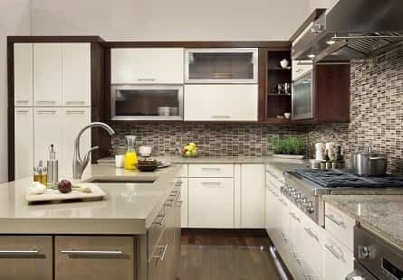 A kitchen fully-furnished with well-decorated items including intricate wooden cabinets with glass doors.