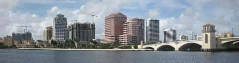 Panoramic view of West Palm Beach showing tall buildings, cranes, bridge, vegetation, and flowing river.