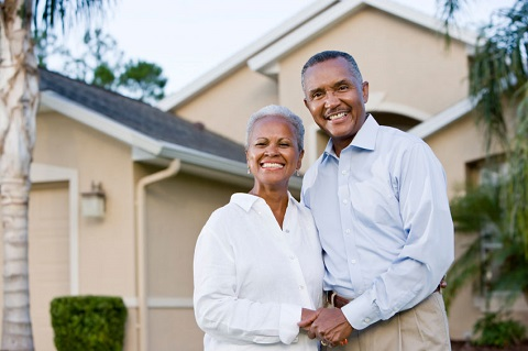 A senior adult couple smiling happy in front of their home. They are holding their hands.