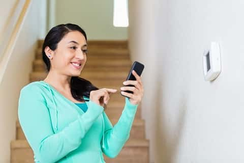 A woman tests her recently-installed alarm using an application on her black smart phone.