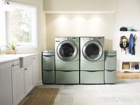 An ideal laundry area, painted white, featuring a rich-colored washing machine, hangers and other items.