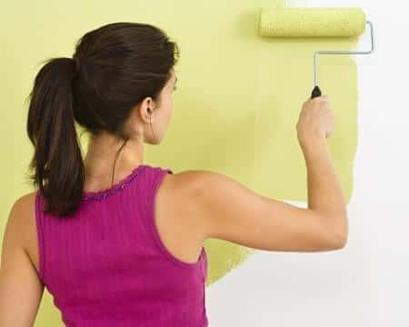 A female painter on purple top using a paint roller to smear the wall with yellow paint