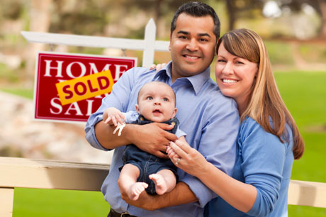 A couple smiling in front a board that shows that they just sold their home. The man is holding their baby while his wife has her arm on him.