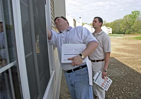 A chubby man in front of a slim man with file in hand inspecting the windowsill of a newly constructed home.