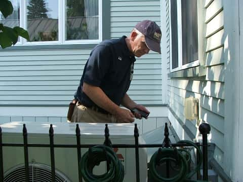 A man inspecting the installation of an air conditioner behind a white painted wooden home.