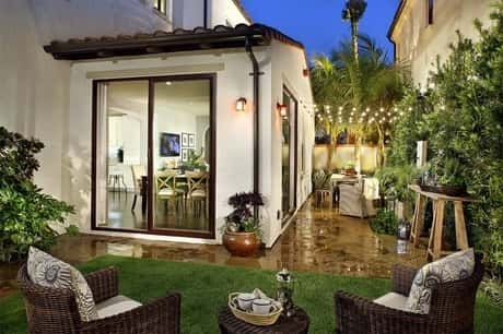 Lavishly decorated and lighted white building with glass door has chairs and tables brilliantly arranged around it.