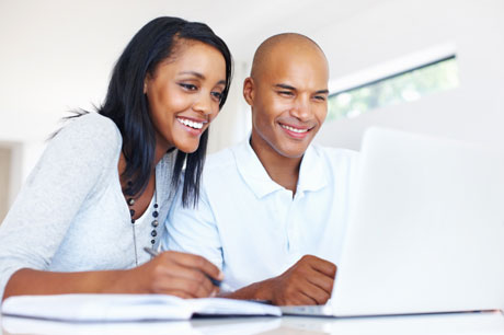 A black couple looking at a white couple and smiling, with a woman holding a pen to a book beside her.
