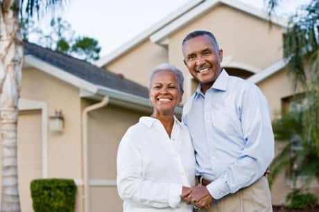 An elderly couple smiling at the camera as they hold hands and stand in front of their home.