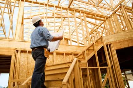 Construction supervisor half way up a staircase holding a sheet of paper to compare the wood construction with the work plan.
