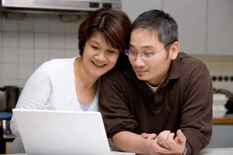 An Asian couple examining information on a laptop computer with the woman leaning her head on the man.