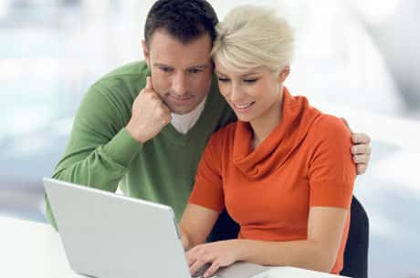 Young couple looking into a laptop.  The man is standing while he places a hand on his partner's shoulders.