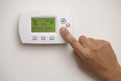 Finger pressing down the down button of a thermostat that controls the temperature of the home.