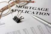 A zoomed-in view of a mortgage application with a silver pen, a pair of specs and a document pin on the document.