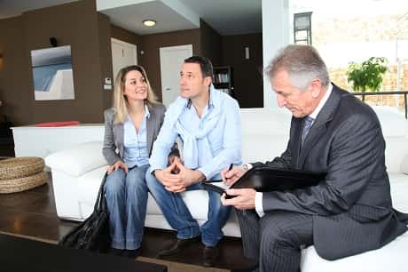 A couple sitting on a sofa with an elderly agent, as they take a look at their new home.