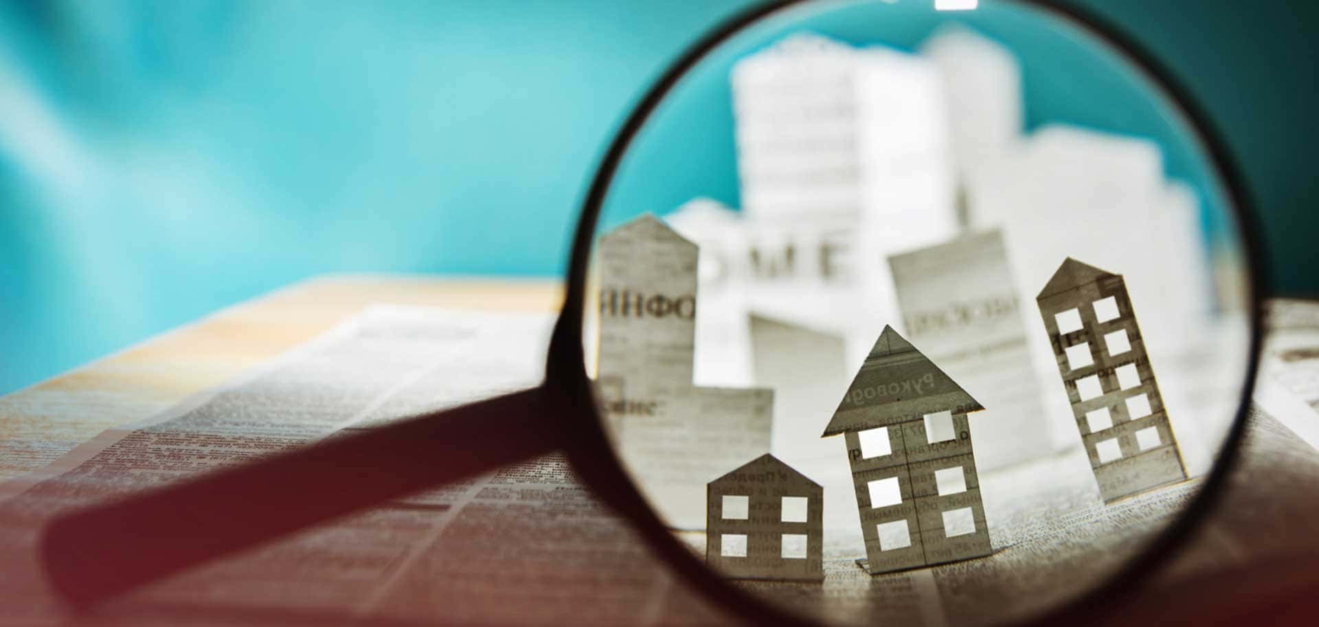 Magnifying glass over paper homes, indicating the discovery of a new house