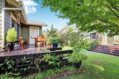 View of guest house with wooden deck and nicely trimmed garden. Located in the Northwest region of the United States.