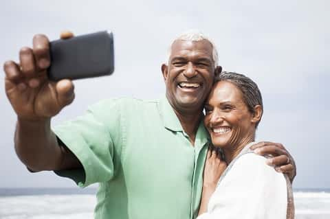 Senior African American couple smiling together on the beach.