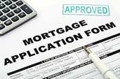 "Mortgage application form with the word ""approved"" stamped in light blue."