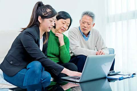 An Asian senior couple meet with a financial planner to determine if they can comfortably retire.