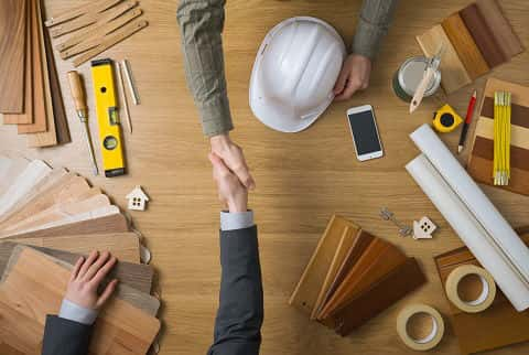 Homebuilder and homebuyer shaking hands top view close up, desktop with work tools and wood swatch on background