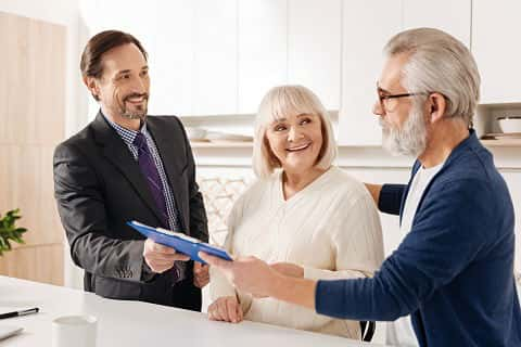 Smart confident upbeat lender meeting with older couple of clients while working and giving professional consultation about financing a house.