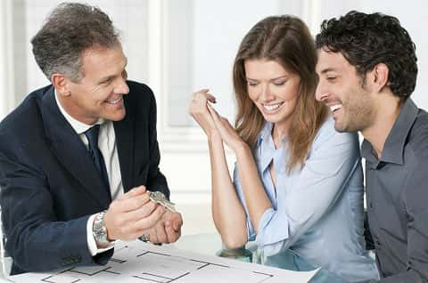 Couple looking at floor plan with real estate agent holding keys to their new home.