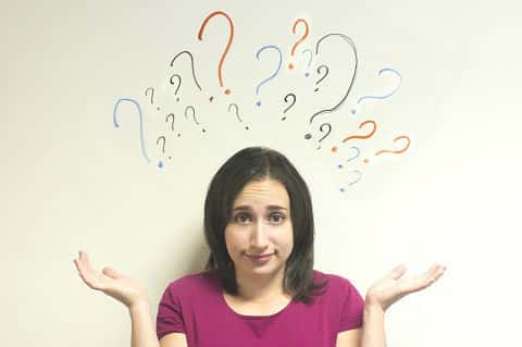 Woman looking confused with her hands up in the air and question marks above her head.
