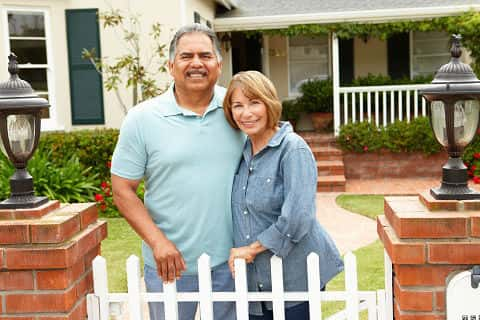A senior Hispanic couple stand smiling outside one of their homes in front of a white picket fence.