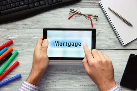 Top view shot of businessman using modern digital tablet and pressing on Mortgage button.