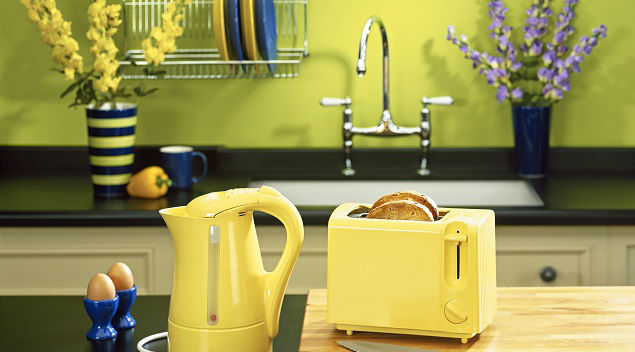 A yellow wall and yellow kitchen accessories add pop to a kitchen.