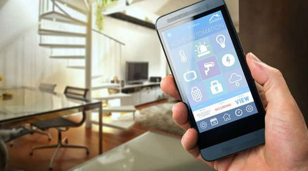 Hand holding a smartphone with apps to control smart tech in the home