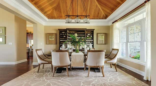Three sets of large windows in the Herring Point Plan by Schell Brothers provide not only natural lighting in the home's formal dining room, while a wood recessed ceiling adds a touch of dramatic elegance. Located at the  Senators in Lewes, DE.