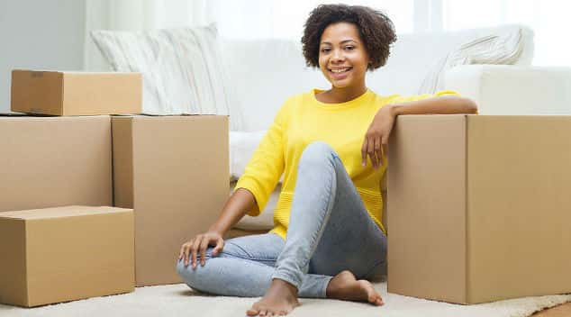 Young African-American female sitting among moving boxes in new home
