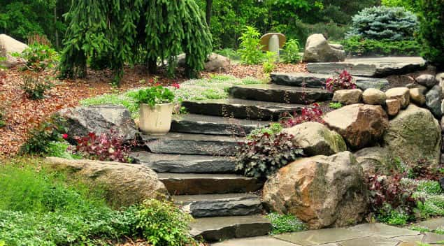 Rocks, stones, bricks, oh my! A nicely designed landscape adds form and function to any outdoor landscape, like this outdoor stairway and walkway created with Bluestone with boulders.
