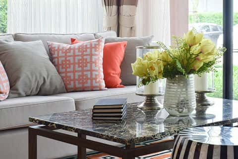 Black books, yellow flowers and other decorative items sit on a marble top table next to a gray sofa set with salmon, gray and white throw pillows.