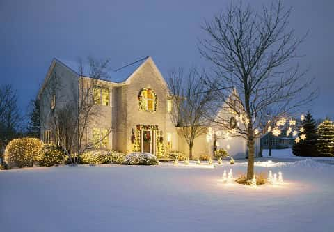A snow-covered two-story home with all-white Christmas lights for the holidays.